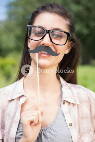 Pretty brunette smiling at camera with fake mustache