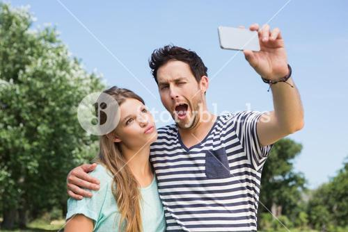 Cute couple in the park taking selfie