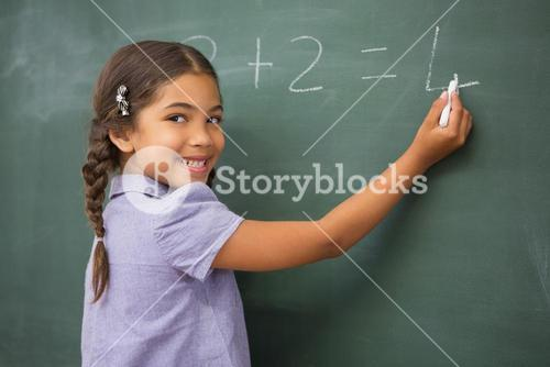 Pupil writing numbers on a blackboard