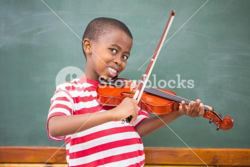 Happy pupil playing violin in classroom