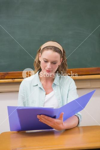 Teacher reading papers at her desk