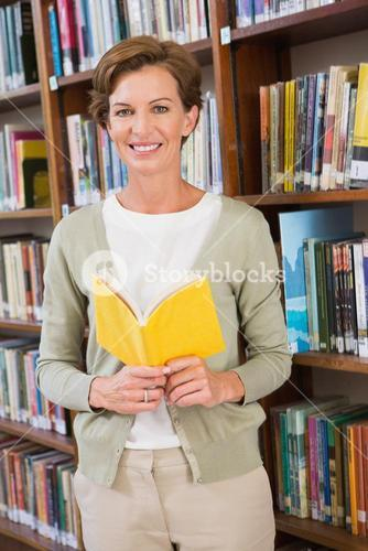 Teacher reading book at library