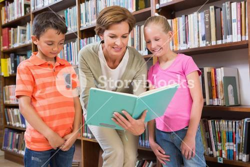 Teacher reading book with pupils at library