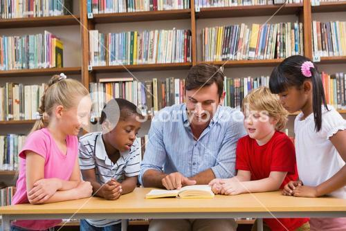 Teacher reading book to pupils at library