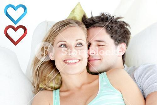 Composite image of portrait of a hugging couple sitting on a sofa in the livingroom