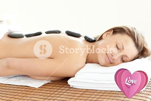 Composite image of radiant woman with hot stones on her back
