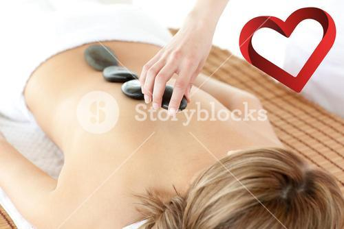 Composite image of radiant woman having a stone therapy