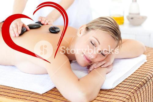Composite image of pretty young woman receiving a massage with hot stone