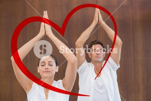 Composite image of peaceful couple in white doing yoga together with hands raised
