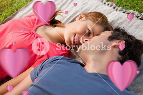 Composite image of woman looking into her friends eyes while lying on a quilt
