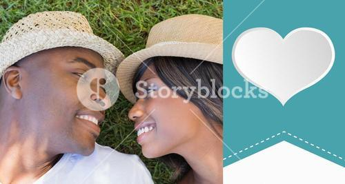 Composite image of happy couple lying in garden together