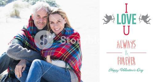 Composite image of happy couple wrapped up in blanket sitting on the beach
