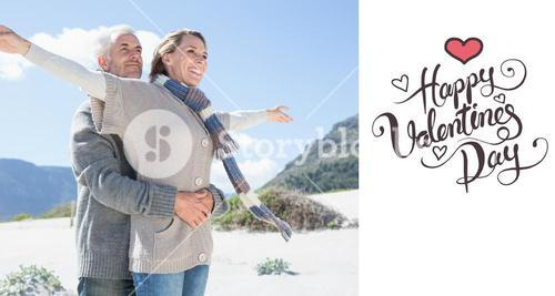 Composite image of carefree couple hugging on the beach in warm clothing
