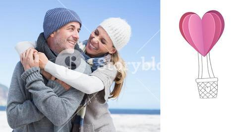 Composite image of attractive couple hugging on the beach in warm clothing
