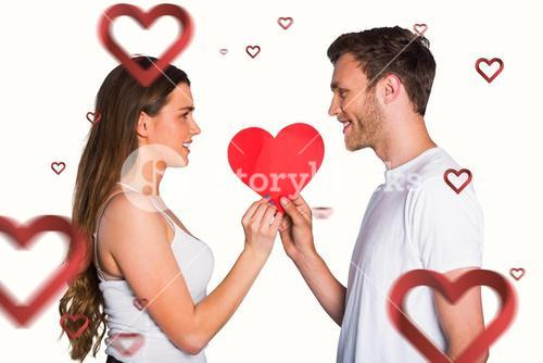 Composite image of romantic young couple holding heart