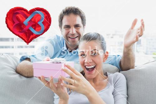 Composite image of man surprising his delighted girlfriend with a pink gift on the sofa