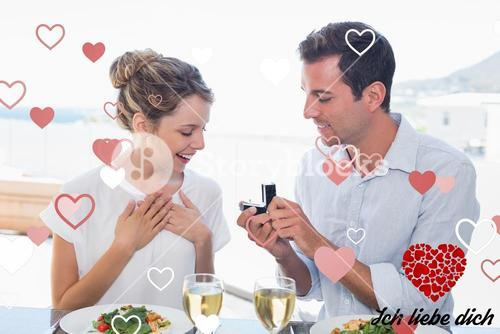 Composite image of man surprising woman with a wedding ring at lunch table