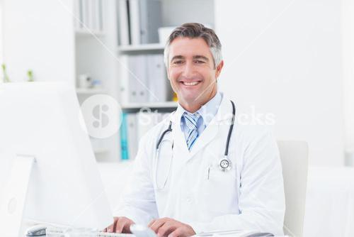 Confident doctor using computer in clinic