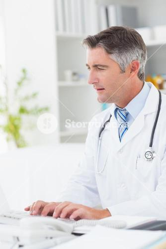 Doctor using computer keyboard at table