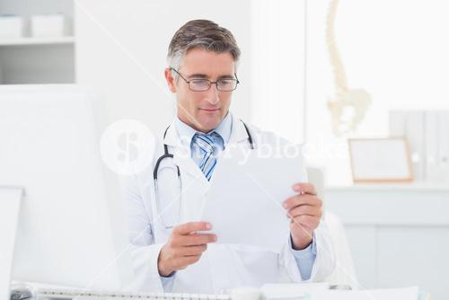 Doctor reading document in clinic