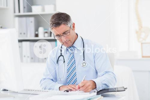 Male doctor writing on paper at table