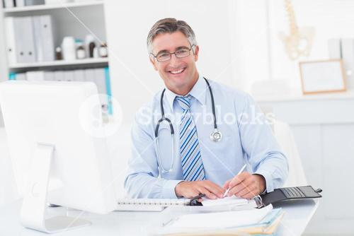 Happy smart doctor writing on paper