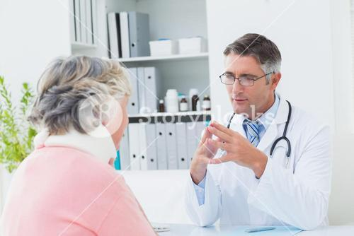 Doctor discussing with female patient wearing neck brace