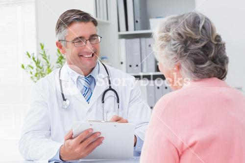Smiling doctor writing prescriptions for patient