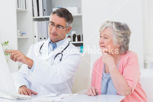 Doctor showing reports to senior patient on computer