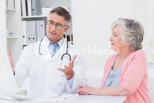 Doctor explaning reports to patient on computer