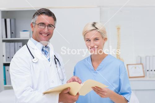 Happy doctor and nurse holding report