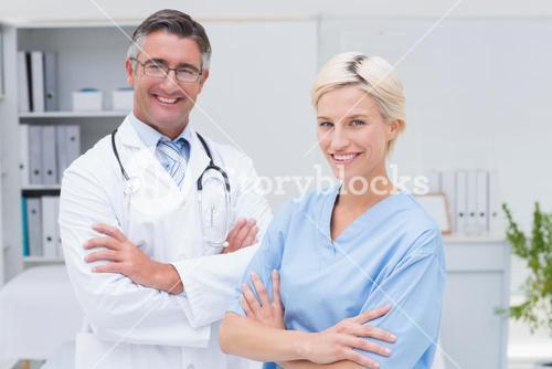 Nurse and doctor standing arms crossed at clinic