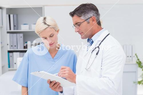 Doctor and nurse discussing over notes on clipboard