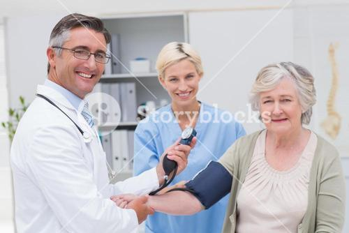 Doctor and nurse checking patients blood pressure