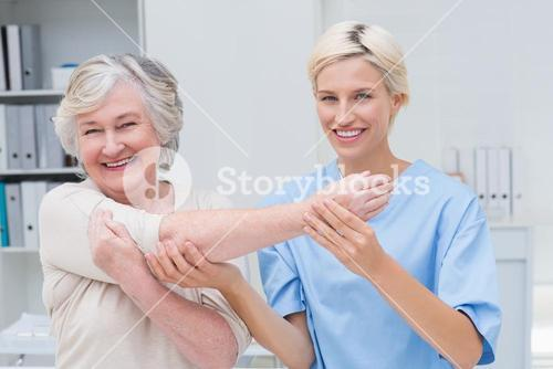 Smiling nurse assisting senior patient in raising arm
