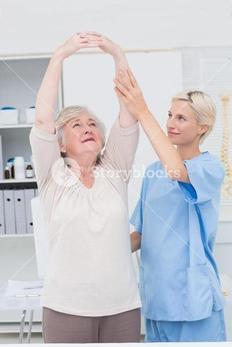 Nurse assisting female patient in raising arms