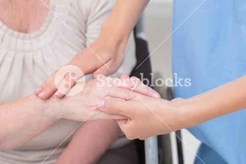 Nurse checking flexibility of patients wrist in clinic