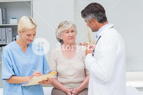 Doctor consoling patient while nurse writing reports