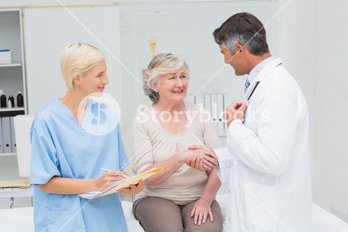 Doctor and patient shaking hands while nurse writing reports