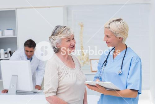 Nurse discussing with patient while doctor using computer