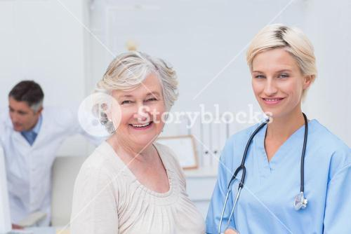 Nurse and senior patient smiling in clinic