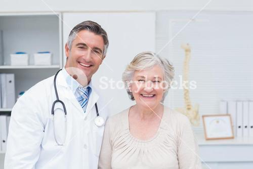 Happy male doctor and female patient in clinic