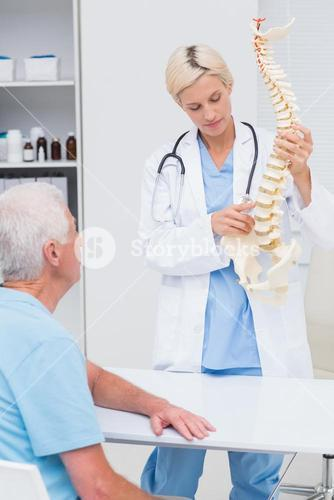 Doctor explaning spine model to patient in hospital