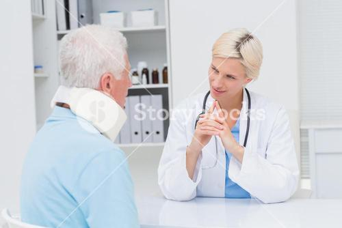 Doctor looking at senior patient wearing neck brace