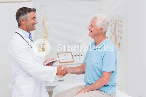 Male doctor and senior patient shaking hands