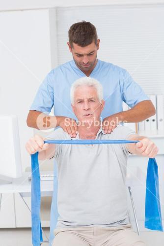 Physiotherapist assisting senior man in exercising with resistance band