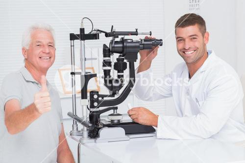 Senior man showing thumbs up while sitting with optician