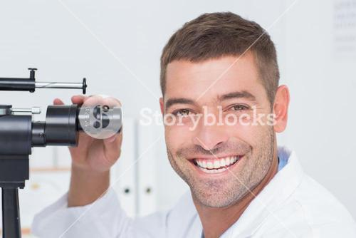 Happy optician using slit lamp in clinic