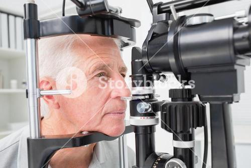 Man looking into slit lamp
