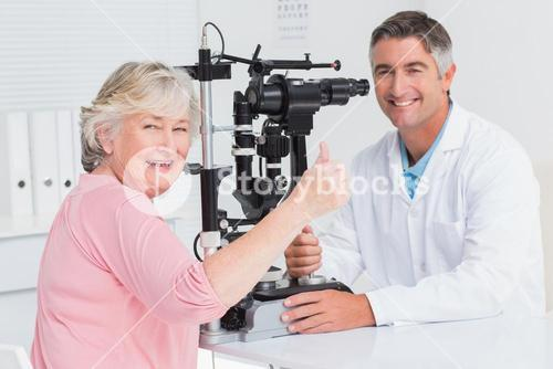 Senior patient gesturing thumbs up while sitting with optician